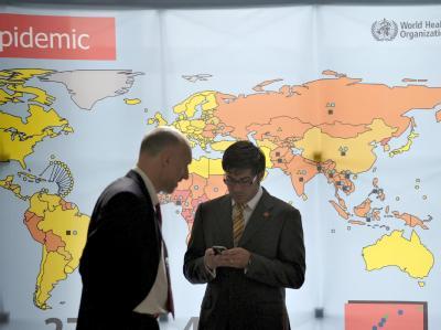 Delegierte der Weltgesundheitsversammlung (WHA) in Genf vor einer Weltkarte.