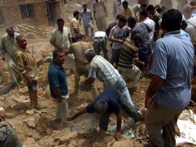 Überlebende suchen nach dem Bombenanschlag bei Kirkuk in den Trümmern nach weiteren Opfern.
