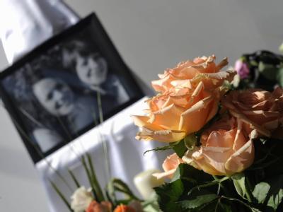 Blumenschmuck und ein Erinnerungsbild umrahmen die Trauerfeier in Wolfsburg.