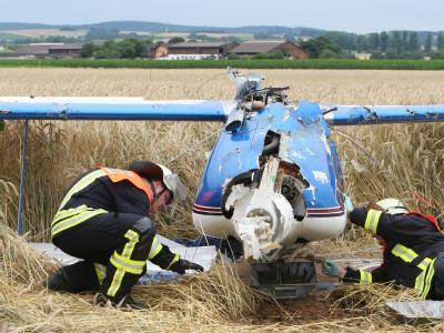 Nach einem missglückten Looping untersuchen Feuerwehrleute das Wrack des Doppeldeckers. Der Pilot hatte nach einem Flugfehler ein Auto erfasst.