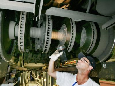 Ein Nachschauschlosser kontrolliert unter einem ICE-Triebwagen die Bremsanlage.