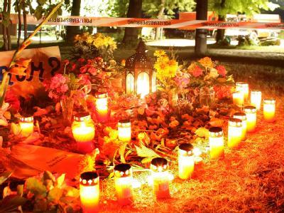 Blumen und Kerzen stehen vor der Polizeiabsperrung am Unglücksort in Nachterstedt (Salzlandkreis). (Archivbild)