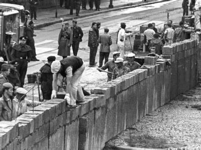 Unter der Aufsicht von bewaffneten Volkspolizisten errichtet eine Ostberliner Maurerkolonne am 18.8.1961 am Potsdamer Platz eine mannshohe Mauer.