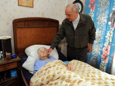 Jörg-Michael Zentgraf neben dem Bett seiner pflegebedürftigen, 103 Jahre alten Mutter Eleonore.