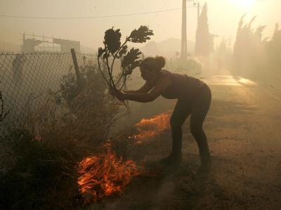 Oft mit einfachsten Mitteln versuchen Freiwillige der Flammen Herr zu werden.