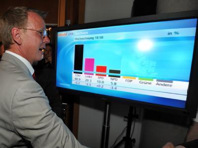Der Spitzenkandidat der Linken bei der Landtagswahl in Thüringen, Bodo Ramelow, steht im Landtag von Erfurt vor einem Fernsehmonitor mit den Wahlergebnissen.