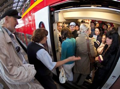 Eine Mitarbeiterin der Deutschen Bahn (DB) versucht Fahrgäste in Berlin zu beruhigen, die in einen überfüllten Regionalzug einsteigen wollen.