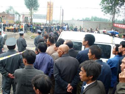 Chinesen warten vor dem Kohlebergwerk, in dem zahlreiche Bergarbeiter ums Leben gekommen sind.