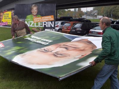 Zwei Arbeiter demontieren ein Wahlplakat mit der Abbildung des SPD-Spitzenkandidaten Frank-Walter Steinmeier in Berlin.