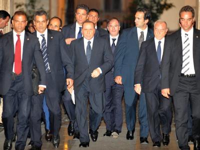 Italiens Ministerpräsident Berlusconi verlässt seine Residenz in Rom umgeben von seinen Vertrauten und Bodyguards.