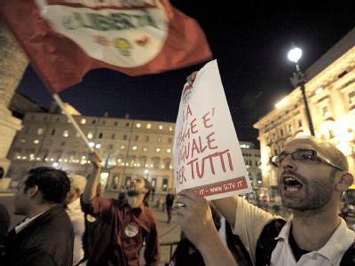 Ein Demonstrant vor dem Palazzo Chigi in Rom hält ein Poster mit dem Spruch