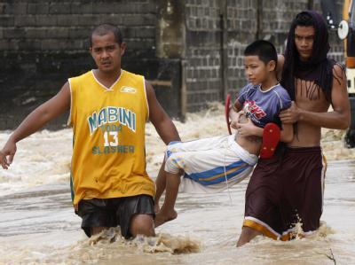 Rette sich wer kann: Mehrere kurz aufeinanderfolgende heftige Stürme haben auf den Philippinen eine Katastrophe ausgelöst. Flüsse traten über ihre Ufer wie hier in Rosales.