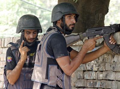 Polizeibeamte sind vor dem umkämpften Gebäude in der Stadt Lahore in Stellung gegangen.