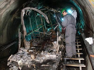 Das Archivbild vom 16.11.2000 zeigt Bergungsarbeiter bei der Inspektion von Überresten der verbrannten Tunnel-Gletscherbahn.