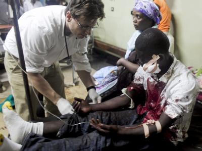 Ein Arzt behandelt einen verletzten: In der ugandischen Hauptstadt Kampala sind bei einem Bombenanschlag mehr als 64 Menschen getötet worden.