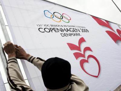 In Kopenhagen befestigt ein Helfer ein Banner für das IOC-Treffen an einem Absperrgitter.