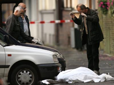 Kriminalpolizisten untersuchen den Tatort in der Innenstadt von Duisburg.