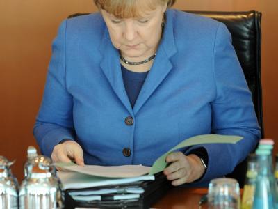 Bundeskanzlerin Angela Merkel (CDU) liest im Kanzleramt in Berlin im Kabinett in einer Akte. Foto: Maurizio Gambarini
