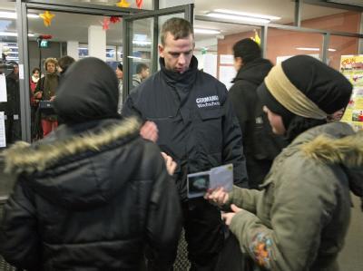 Ein Mitarbeiter eines Wachschutzunternehmens kontrolliert im Eingangsbereich einer Schule im Berliner Stadtteil Neukölln Schülerausweise (Archiv).