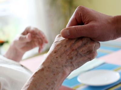 Ein Altenpfleger hält die Hand einer Patientin