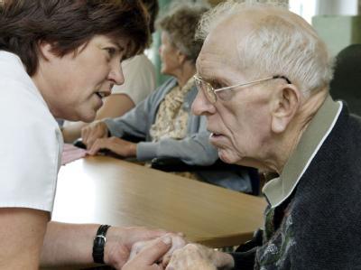 In einem Leipziger Heim kümmert sich eine Pflegerin um einen Demenzkranken (Archivbild).