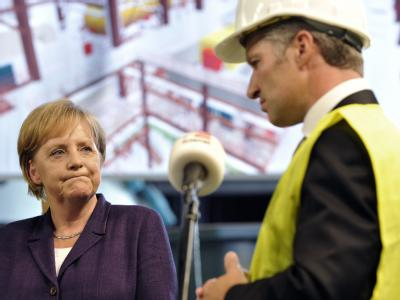 Bundeskanzlerin Merkel verfolgt auf der Baustelle des Trianel-Steinkohlekraftwerks in Lünen eine Ansprache von Sven Becker, dem Sprecher der Trianel-Geschäftsführung.