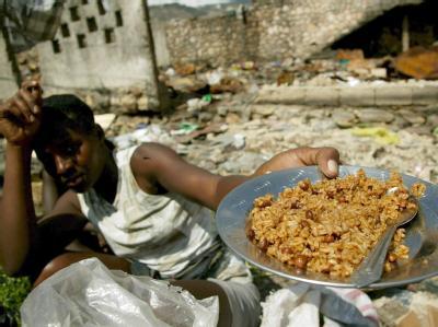 Eine haitische Frau zeigt in Port-au-Prince einen Teller mit einem Reisgericht - dem Hauptnahrungsmittel in Haiti (Archivbild). Die heimischen Bauern können nur noch knapp die Hälfte des Nahrungsmittelbedarfs decken.