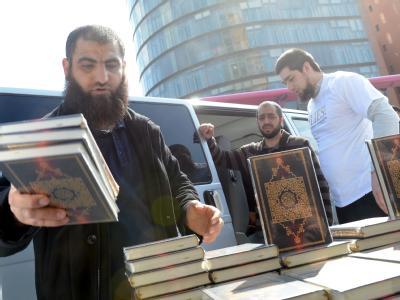 Salafisten, die vom Verfassungsschutz als radikal-islamisch eingestuft werden, beim Verteilen von kostenlosen Koran-Exemplaren in Berlin. Foto: Britta Pedersen