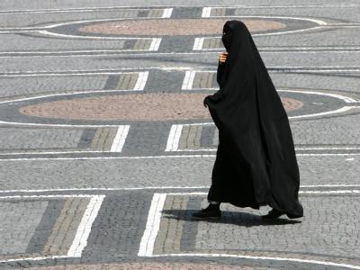 Eine Frau in einer Burka geht durch München. In Frankreich soll das streng islamische Kleidungsstück künftig verboten sein.