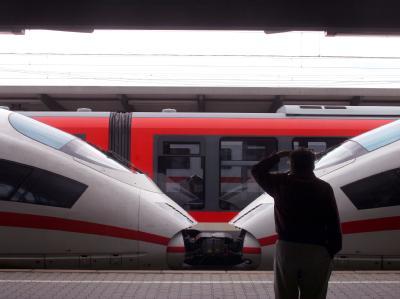 Ein Reisender blickt auf dem Augsburger Hauptbahnhof auf einen stehenden ICE und einen Regionalzug. (Archivbild)