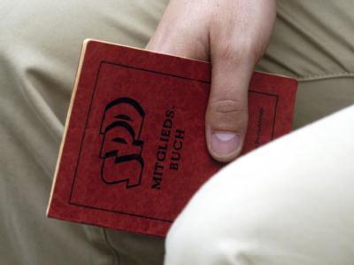 Ein SPD-Anhänger hält sein Parteibuch in der Hand. (Symbolbild) Für den Ausschluss von Parteimitgliedern hat das Parteiengesetz hohe Hürden errichtet.