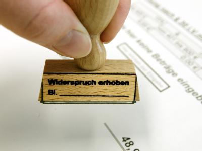 In der Widerspruchsstelle für Hartz IV der Arbeitsgemeinschaft Leipzig hält eine Mitarbeiterin einen Stempel für Eingänge von Widersprüchen in der Hand.