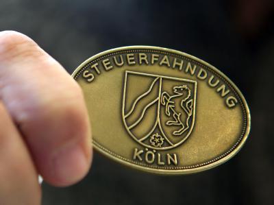 Ein Steuerfahnder in Köln zeigt seine Dienstmarke: Die Union will striktere Steuerregeln auferlegen. Damit soll unter anderem die Gründung von Scheinbanken in Steueroasen unterbunden werden (Symbolbild).