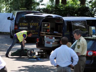 Ein Beamter der Kriminalpolizei steht am 09.06.2010 in Hagnau am Bodensee vor dem Wagen einer ermordeten Taxifahrerin.