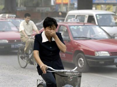 Eine Fahrradfahrerin versucht, sich auf einer Straße in Peking gegen den Smog zu schützen (Archivfoto vom 15.9.2003).