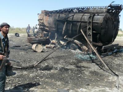 Das ausgeglühte Wrack eines der Tanklaster wird von einem afghanischen Polizisten bewacht.