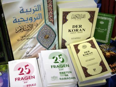 Eine deutschsprachige Ausgabe des Koran und weitere religiöse Schriften. Foto: Peer Grimm/Archiv