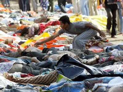 Ein Mann sucht unter Hunderten von Leichen in Banda Aceh nach seinem Sohn (Archivfoto vom 28.12.2004).