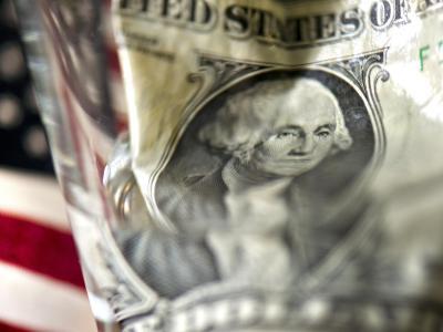 Durch ein Wasserglas verzerrt: Dollar-Banknote. Foto: Arno Burgi