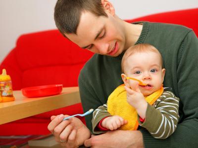 Ein junger Vater füttert seinen Sohn: Mehr als jeder vierte Vater eines neugeborenen Kindes geht inzwischen in Elternzeit. Foto: Uwe Anspach/Archiv