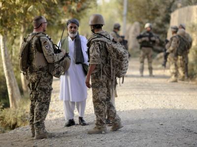 Ein Bundeswehrsoldat (l) und ein Dolmetscher (r) sprechen bei Kundus mit einem afghanischen Mann. Foto: Maurizio Gambarini/Archiv
