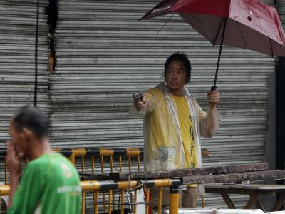 Ein Ladenbesitzer verteidigt in Tacloban sein Geschäft mit einer Pistole gegen Plünderer. Foto: Francis R. Malasig