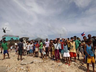 Behwohner des Dorfes Hernani warten auf Nahringsmittel. Foto: Dennis Sabangan