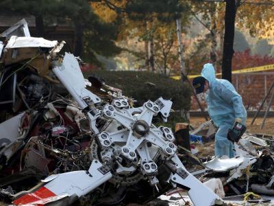 Ein Ermittler untersucht die Trümmer des verimglücktenHelikopters. Foto: Jeon Heon-Kyun