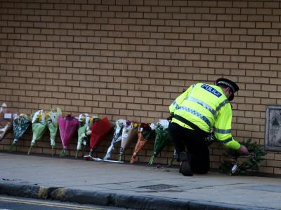 Ein Polizist legt in Glasgow Blumen für die Pfer nieder. Foto: Andrew Milligan