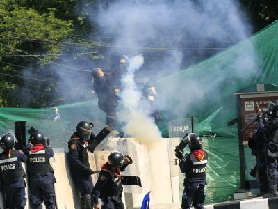 Polizisten schleudern eine Tränengasgranate inRichtung der Demonstranten. Foto: Narong Sangnak