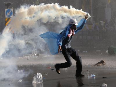 Ein Demonstrant schleudert eine Giftgaskartusche zurück inRichtung Polizei. Foto: Rungroj Yongrit