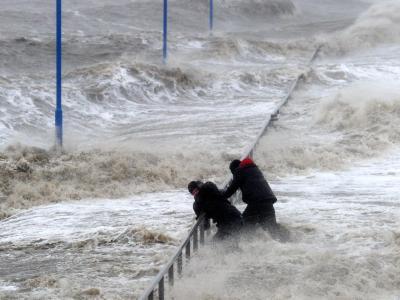 Zwei Männer halten sich auf dem überfluteten Fähranleger in Dagebüll an einem Geländer fest. Foto: Carsten Rehder