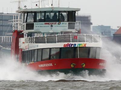 Eine Hafenfähre ist im Hamburger Hafen auf der aufgewühlten Elbe unterwegs. Foto: Bodo Marks