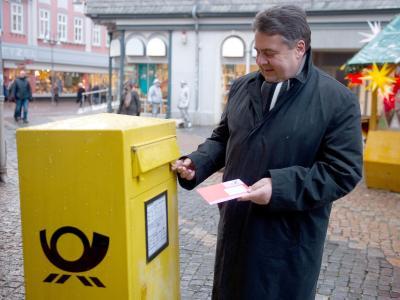 SPD-Chef Sigmar Gabriel wirft einen Briefumschlag mit seinem Stimmzettel für den SPD-Mitgliederentscheid in den Briefkasten. Foto: Swen Pförtner